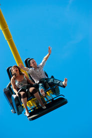 stock photo of carnival ride  - Happy young couple riding on the attraction - JPG