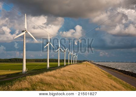 Dutch Windturbines And A Cloudscape In The Last Sunlight Of A Summer Evening