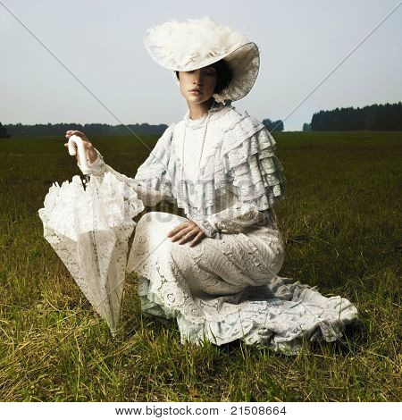 Photo of beautiful woman in vintage dress for promenade