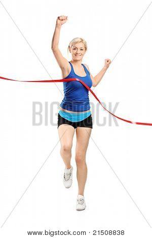 Full length portrait of a female runner running towards a finish line isolated against white background