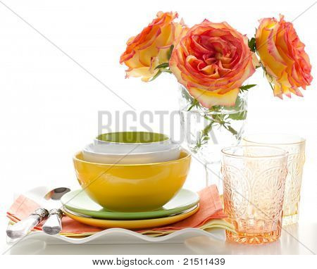 Arrangement of three colorful bowls, plates ,glasses and rose