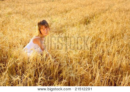 Young woman in white dress sitting in the middle of a field with yellow ripe wheat