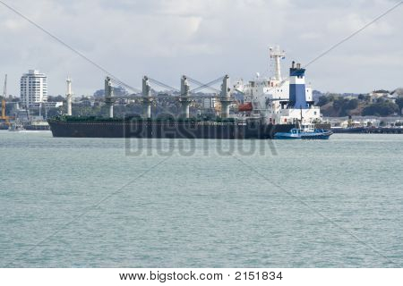 Container Ship Being Manoeuvred By A Tug Boat