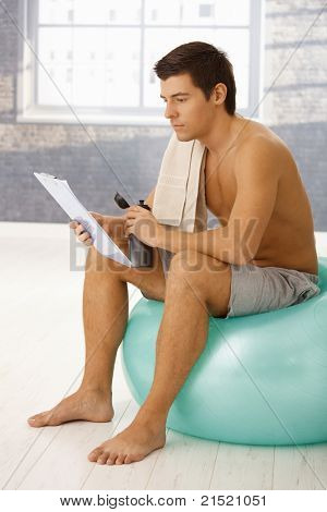 Young man sitting on gym ball in break of training, drinking sports drink and checking training program on clipboard.?