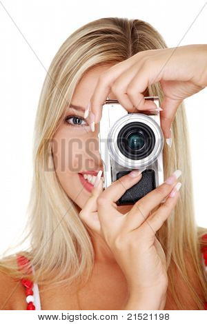 Young beautiful smiling blond woman holding a micro four thirds photo camera. Isolated over white background.