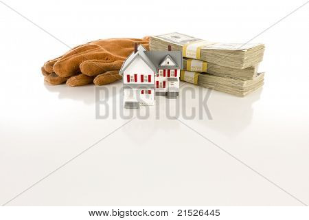 Stacks of One Hundred Dollar Bills, Leather Work Gloves and Small House on Slight Reflective Surface.