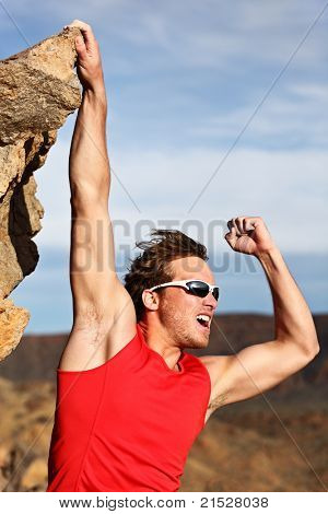 Success concept - man climbing, hanging on edge showing strength and muscles. Strong successful male climber.