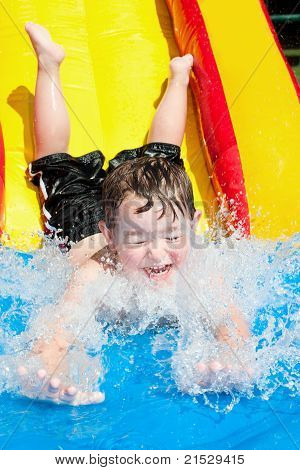 Young boy  splashes into pool after going down water slide