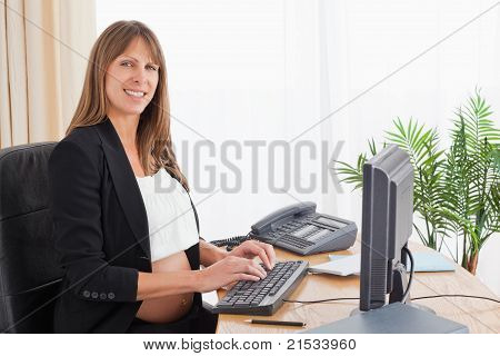 Lovely Pregnant Woman Working With A Computer