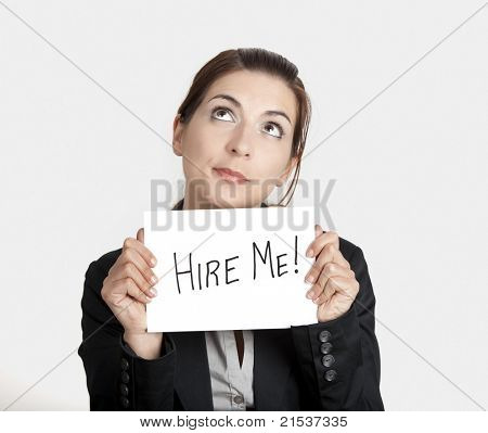 """Business woman holding a card board with the text message """"Hire me"""""""