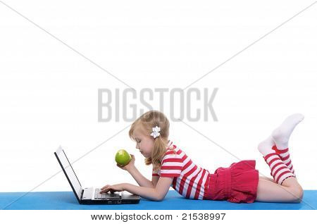 girl with an apple and laptop on rug
