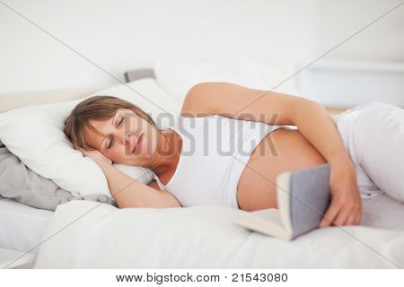Beautiful Pregnant Woman Reading A Book While Lying On Her Bed