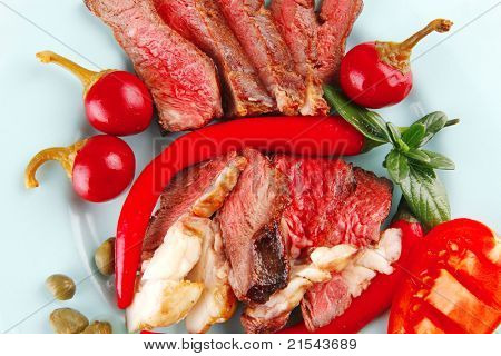 roast beef slices on blue dish over white