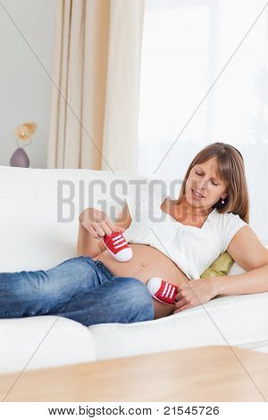 Lovely Pregnant Female Playing With Red Baby Shoes While Lying On A Sofa