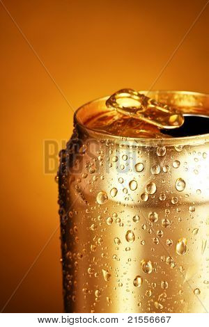 gold tin can on a yellow background. Focus on nearest water drops