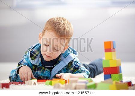 Schöne Toddler Boy spielen mit Erstellen von Cubes zu Hause Handauflegen Boden.?