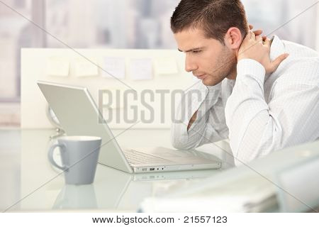 Young man working on laptop, looking tired, sitting at desk.?