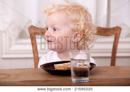A young boy at the lunch table, looking off camera and smiling