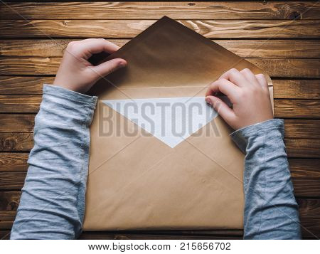 poster of A large brown envelope holds the child's hands. Envelope on a wooden background.