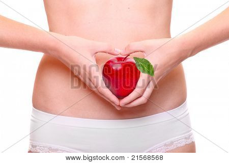 Close up of a young woman holding a fresh ripe apple on her belly. Healthy lifestyle metaphor.