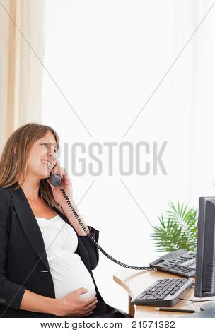 Lovely pregnant woman on the phone while working at the office