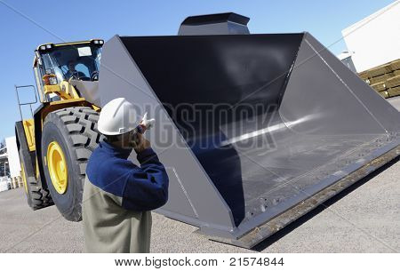 worker and giant bulldozer, digger, construction and excavating machinery