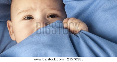 afraid baby under a blue blanket closeup