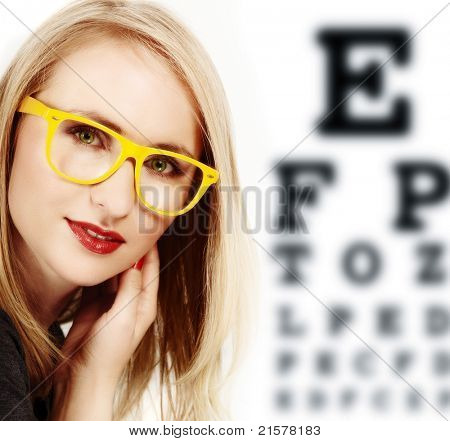 beautiful blond woman with geek yellow glasses and optometry check-up chart.
