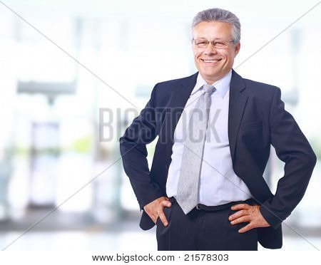 Closeup portrait of satisfied mature businessman in his office with copy space