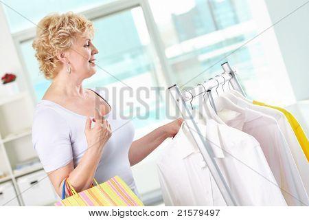 Retrato de mulher envelhecido médio com paperbags, no departamento de vestuário