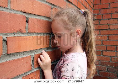 sad girl in front of a brick wall