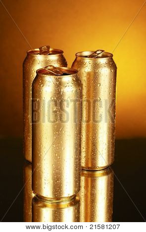 golden tin cans on yellow background with reflection