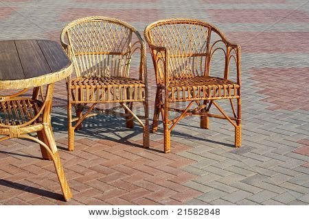 A Pair Of Wicker Chairs And Table