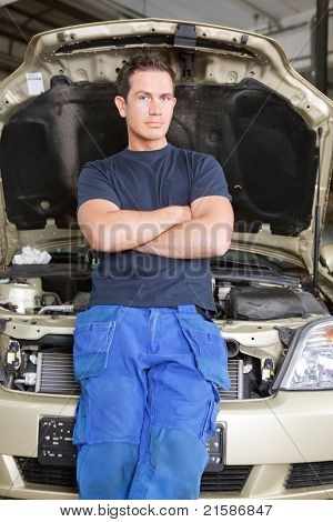 Portrait of a man mechanic leaning against a car looking at the camera
