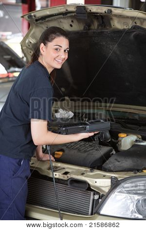 A happy female mechanic looking at the camera using a diagnostic scan tool