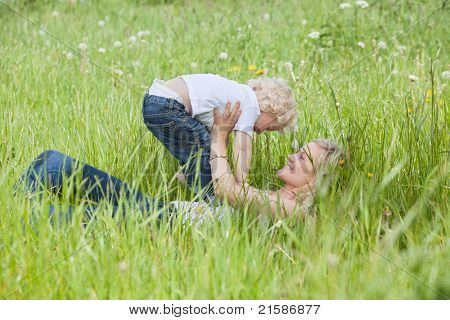 Young pretty woman holding her child while lying on grass