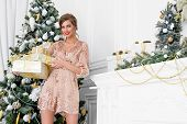 Christmas, winter holidays concept. Beautiful charming woman in evening dress holding a gift box and poster