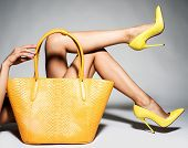Closeup photo of female style yellow leather bag. Part of women legs in beautiful fashionable high h poster