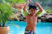image of floaties  - A young Hispanic boy plays by a luxurious pool - JPG