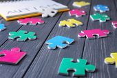 Different puzzles on wooden background. Concept of autism poster