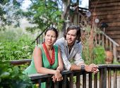 image of native american ethnicity  - Young couple resting at a small bridge in a garden. Shallow DOF focus on girl