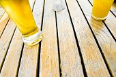foto of growler  - Two glasses of beer on the wooden table - JPG