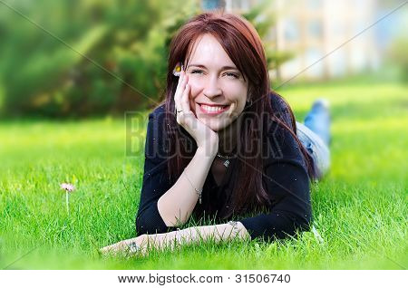 Woman Lying On Green Grass In The Meadow  In Summer