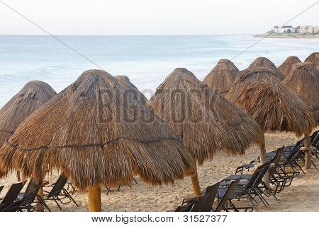 Straw Thatched Beach Huts With Chaise Lounges
