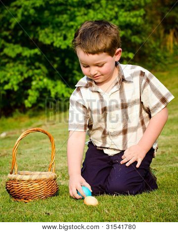 Boy collecting eggs on easter egg hunt