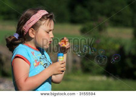 Mädchen bläst Seifenblasen