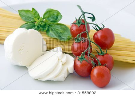 Italian food: spaghetti, mozzarella, cherry tomatoes and basil