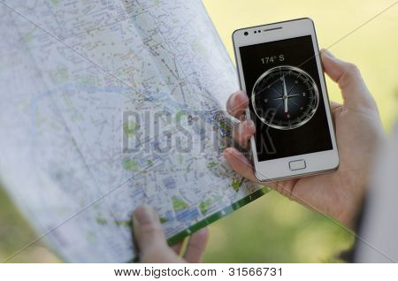 Hands of woman with a map and a compass