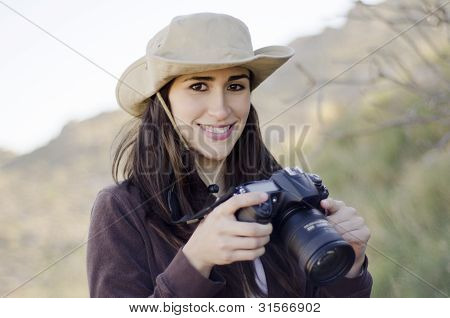 Young woman taking pictures on a hiking trip
