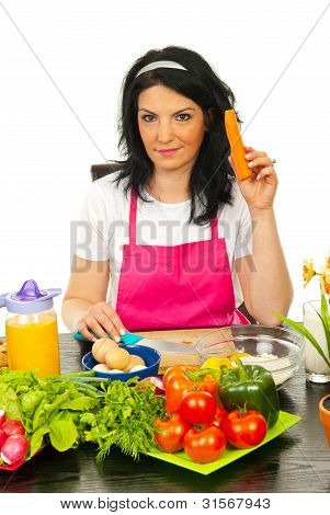 Woman In Kitchen Holding Carrot